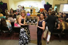 Photo by Marty Cheek Cherisse White, on left, and  Ava Serna display six bottles of vino that were auctioned at the South Valley Wine Auction to raise money for sports.