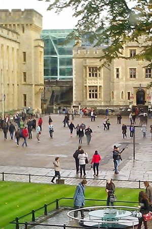 Looking down at a square enclosed on two sides by white stone castle-like buildings and in front by a green lawn with a round table-like structure; many people strolling