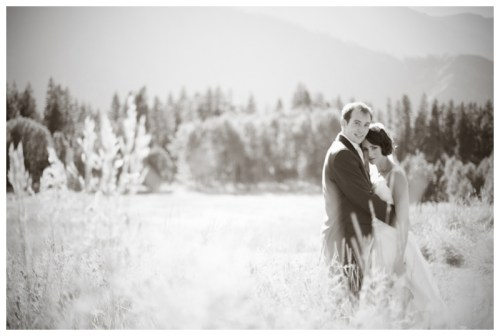 black and white portrait of a bride and groom in a mountain meadow