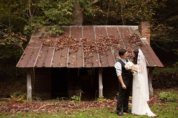 Bride and groom pose in front of a rustic mountain shed in North Carolina