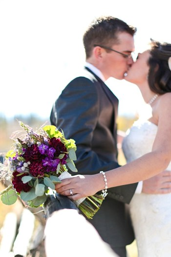 14a-Devils-Thumb-Ranch-wedding-Becky-Young Photography-bouquet-on-fence-kiss