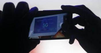An attendee uses his mobile phone to photograph a screen projecting information during a keynote speech at the Mobile World Congress in Barcelona March 3, 2015.