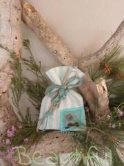 Μπομπονιέρα. Μπομπονιέρα Γάμου πουγκί, βαμβακερό ριγέ εκρού – πετρόλ με διακοσμητικό στοιχείο μουστάκι και δέσιμο από κορδόνι λινάτσα χειροποίητο.