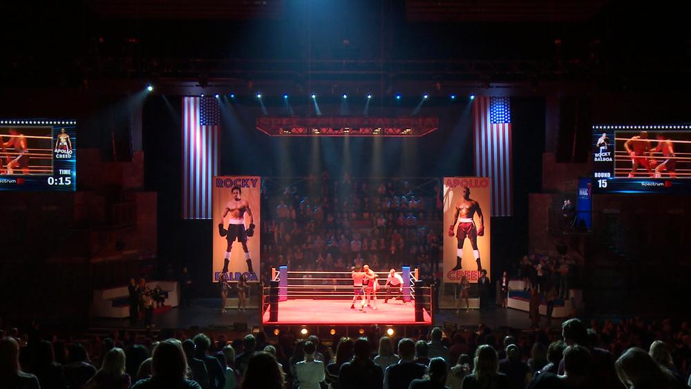 Finálová scéna zápasu s diváky přesazenými na tribunu na jevišti