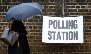 A pedestrian carrying an umbrella to shelter from the rain walks past a sign for a polling station in the European Union (EU) referendum hanging on a wall outside Hanover Primary school in London, U.K., on Thursday, June 23, 2016. Britain began voting Thursday on whether to remain a member of the European Union or split from the 28-nation bloc, a once-in-a-generation decision that will determine the U.K.'s future economic prosperity and the course of the EU. Photographer: Chris Ratcliffe/Bloomberg