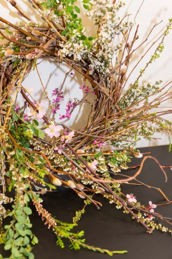 A finished wreath incorporates many of the more delicate flowering shrubs with a central focal point of redbud and plum branches.