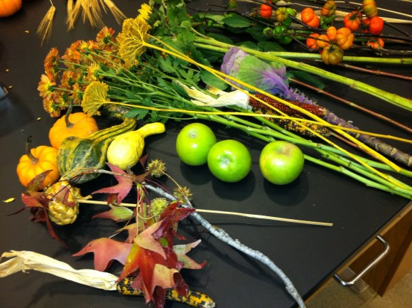 Ingredients for a fall cornucopia include apples, leaves on branches, gourds, and fall flowers.