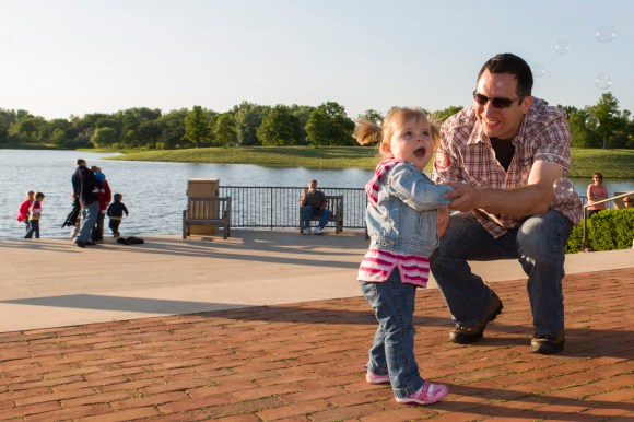 PHOTO: A dad dances with his daughter, who is amazed by some bubbles in the air.
