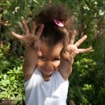 PHOTO: cute girl with muddy hands shows them to the camera.