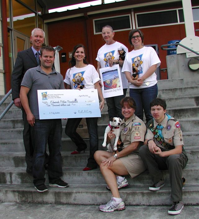 During Tuesday's Edmonds City Council meeting, members of Off Leash Area Edmonds presented the Edmonds Police Foundation with a $2,000 check toward the purchase of a new K-9 dog for the department. Posing outside council chambers after the presentation are, standing from left, Edmonds Police Chief Al Compaan, Police Foundation President David Jones, and OLAE members Julie Nealey, Ann Meyring and Beth Kealey. Sitting are OLAE scoutmaster Shay Hastler, her son Kyle, and their dog Miley. Kyle will be working on the dog park agility course as part of his Eagle Scout project.
