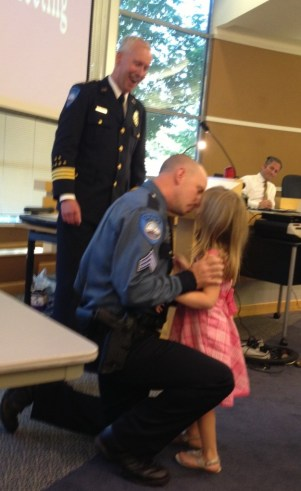 Newly sworn-in Edmonds Police Sgt. Josh McClure gets a kiss from his daughter Ashley after she pins on his badge at Tuesday night's council meeting.