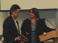 Edmonds City Councilmember Frank Yamamoto receives a plaque and congratulations from Council President Lora Petso Tuesday night. Yamamoto is resigning from his council seat effective Dec. 31.