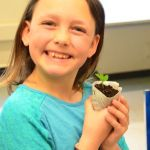 "Maddie Stackhouse is very proud of her sweet pea seedling. ""I'm going right home and put it in the garden,"" she said."
