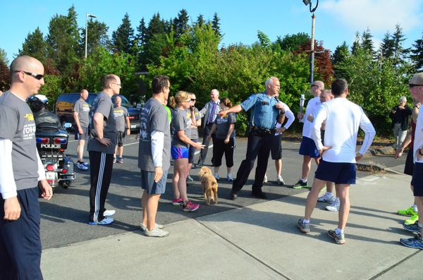Edmonds Chief of Police Al Compaan officiates at the hand-off from Lynnwood torch bearer Officer Matt Keller