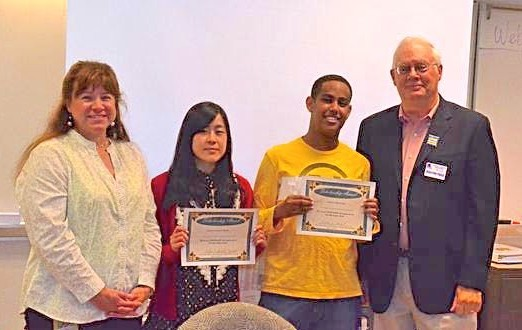 Edmonds Museum Board President Bill Lambert presents two $750 scholarships to Phoung-An NguyenDo, and Markos Mezebu in recognition of their excellent work on building the 2014 Scarecrow Festival website.