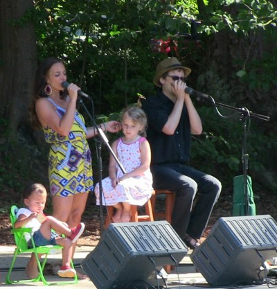 Children from the audience gather on stage as Loretta Lynn's granddaughter Tayla Lynn, center, performs with Eric Tingstad, left, and Sean Devine at  Edmonds City Park Sunday. (Photos by Larry Vogel)