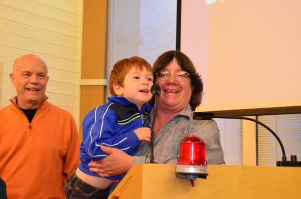 "Edmonds Museum Board member and Scarecrow Festival project manager Dave Buelow looks on as  Councilmember Lora Petso boosts her grandson, four-year-old Augustine ""Gus"" Nishino, to the podium to address the Edmonds City Council."