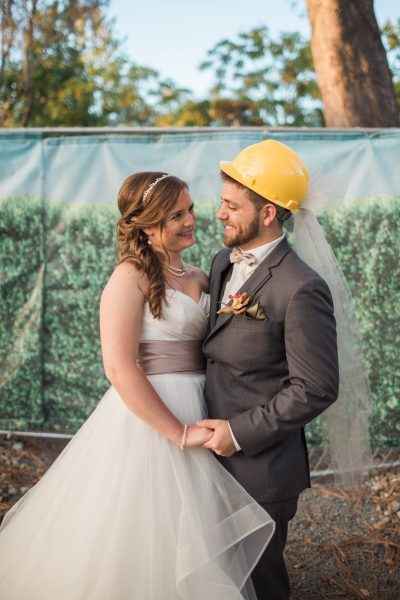 Chris and Natalie pose in front of the fence that surrounded their venue. Natalie's mother provided a veil-decorated hard hat.