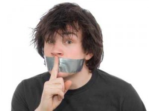 man covered mouth saying shhhhh