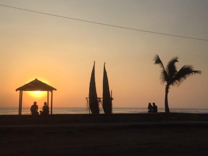 Huanchaco bei Sonnenuntergang mit den traditionellen Einmannbooten der Fischer (Caballitos) im Gegenlicht.