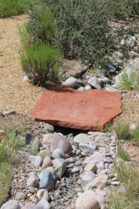 Detail of a dry riverbed swale with a flagstone bridge. Remember, our rains come as large downpours during the monsoon season so our dry riverbed streams work overtime during the rainy season. Make them even more interesting by creating a pathway with a bridge over them.