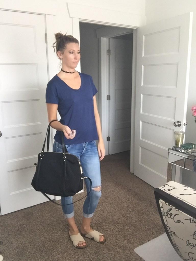 blue t-shirt, distressed denim jeans, sandals, and black shoulder handbag