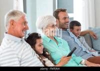 Grandmother and granddaughter watching TV on living room ...