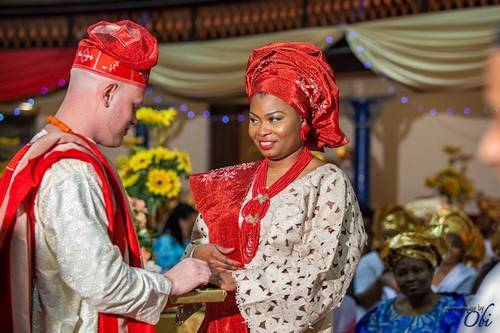 groom putting engagement ring on yoruba bride red white aso oke