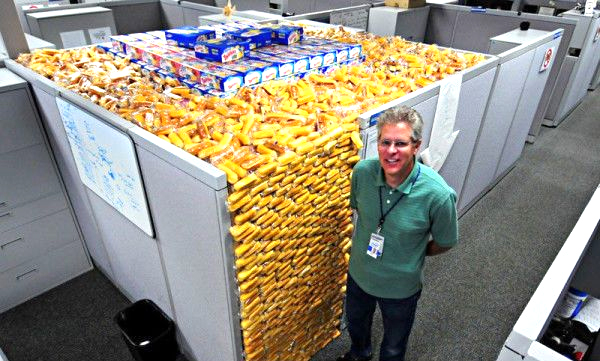 This is a meme of a man who has filled his office cubicle with twinkies
