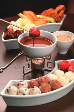 Fondue de chocolate no réchaud servido com sorvete e frutas.