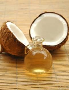 Vidro de Oleo de coco ao lado de um coco cortado ao meio.
