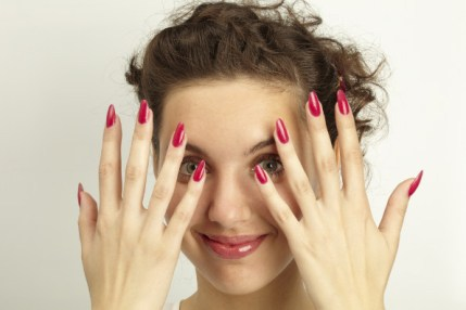 Mulher com as maos em frente ao rosto mostrando as unhas com esmalte vermelho