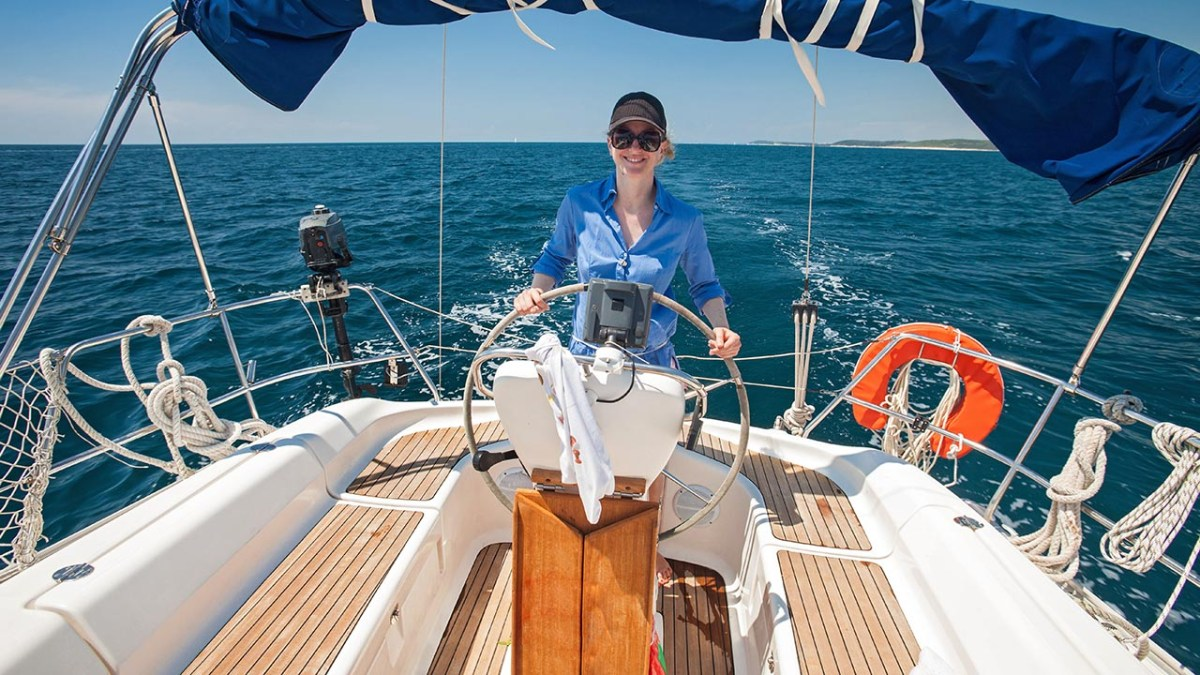 Young woman standing at the helm of a boat against a blue sky