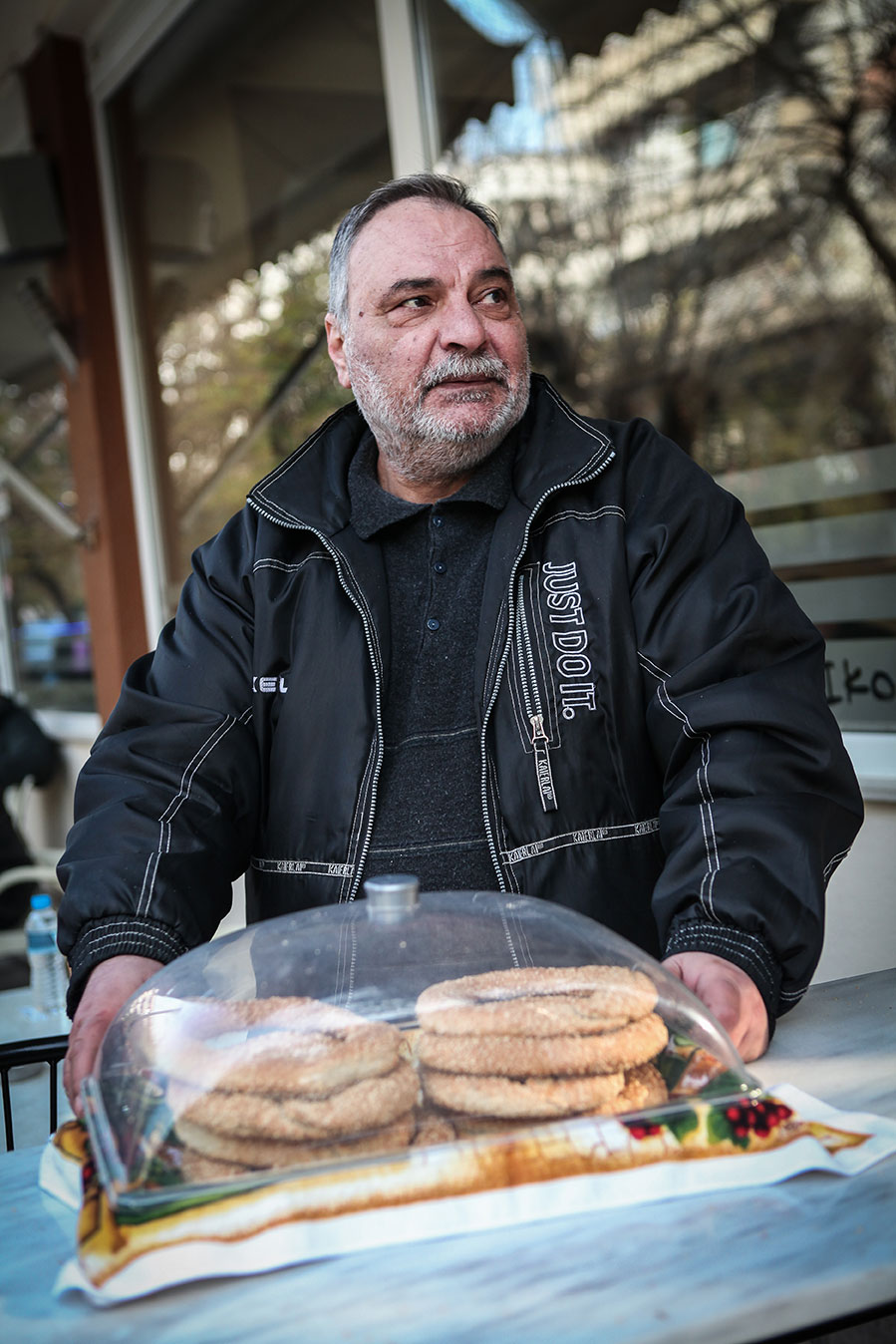 "For over 10 years, Paschalis Batsaris worked as a medical equipment salesman making 3,000–5,000 € per month. In 2012 he found himself unemployed. No longer able to pay his mortgage, he soon lost his home. He currently lives ""here and there, hosted by various friends"" and sells Koulouris (Greek pretzels, a local specialty) on the street to survive. ""When I can make 5–10 € a day, I am very happy""."