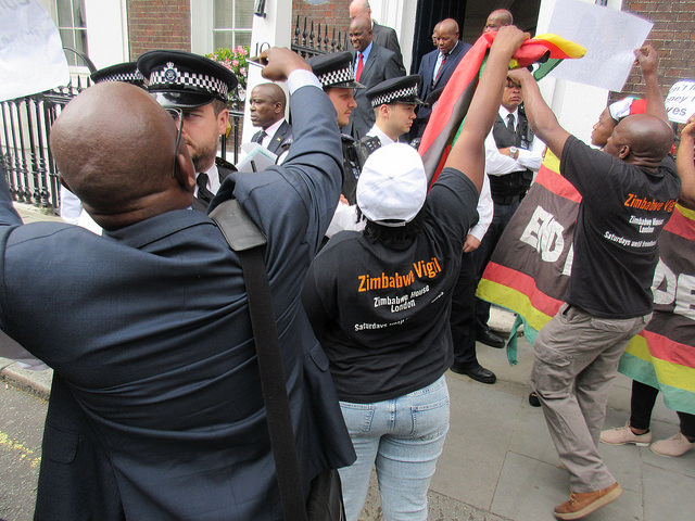 Zimbabwean Finance Minister Patrick Chinamasa was besieged in London by angry Zimbabwean exiles and had to be rescued by a vanload of police.