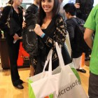 A happy gamer poses with her free backpack and bag full of her new Xbox One.