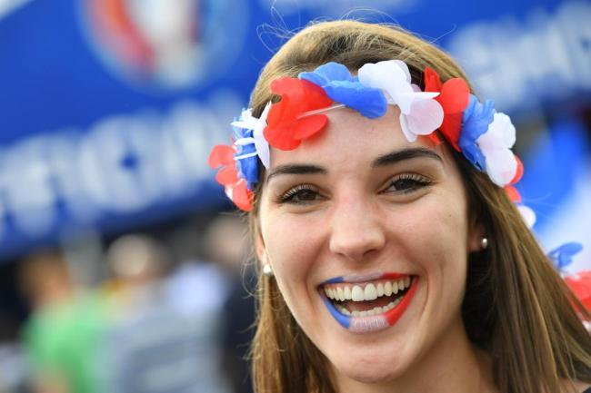 A woman supporting France smiles prior to the Euro 2016 group A football match between France and Romania at Stade de France, in Saint-Denis, north of Paris, on June 10, 2016. / AFP PHOTO / FRANCK FIFE