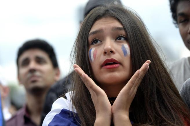 """(FILES) This file photo taken on June 26, 2016 shows a France supporter reacting as she watches the Euro 2016 tournament round of 16 football match between France and Republic of Ireland at the Champ-de-Mars fan zone in Paris. A company of Aix-en-Provence created the """"fanbrush"""", a multiple-line pencil for a make-up in the colours of France. / AFP PHOTO / ALAIN JOCARD"""