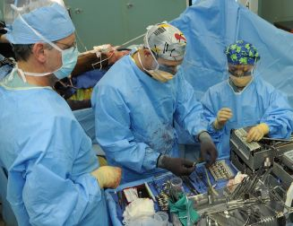 The image shows three surgeons conducting a surgical procedure.