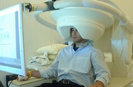 The image shows a person undergoing a MEG scan.