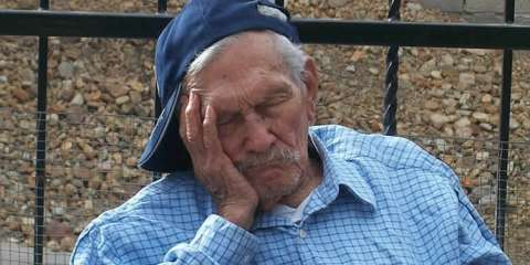 This image shows an old man sleeping on a bench.