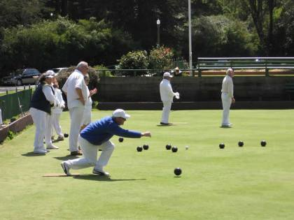 This image shows a group of older people playing lawn bowls.
