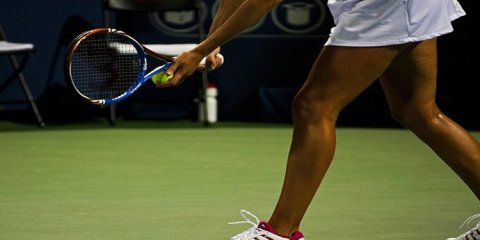 The image shows a female tennis player about to serve a ball.