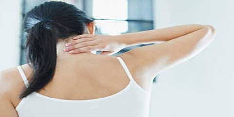 The image shows a woman rubbing the back of her neck.