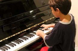 This image shows a young boy playing a piano.