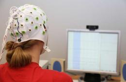 Photo of a woman in a EEG cap looking at a computer monitor.