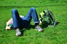Image shows a teenage boy sleeping on the grass.