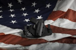Photo of a gun laying on the US flag.