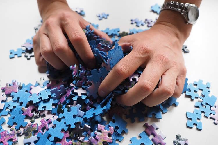 Image shows hands and jigsaw pieces.