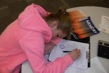 Image shows a girl sleeping next to a memory book.